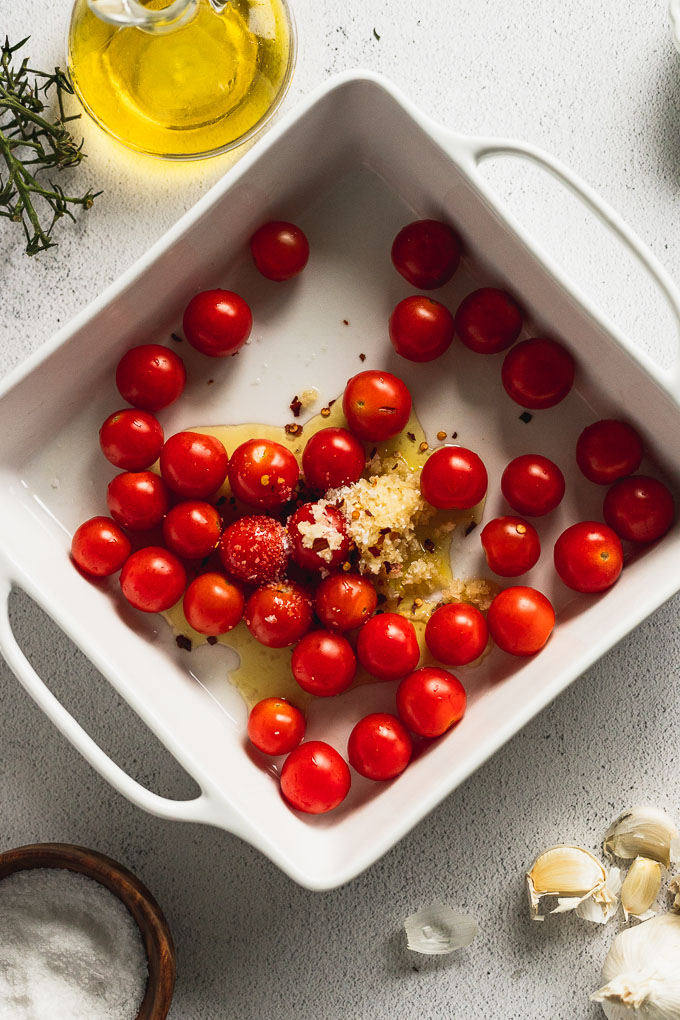 white baking dish with cherry tomatoes, garlic, red pepper flakes, and olive oil