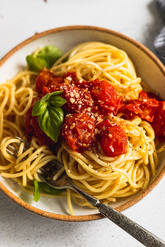 up close white bowl with spaghetti and tomato sauce with fork twirled in pasta