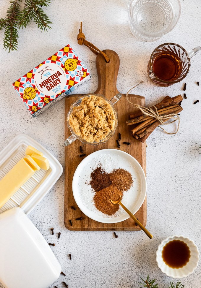 spices, brown sugar, butter, rum, and vanilla extract laid on wood serving tray