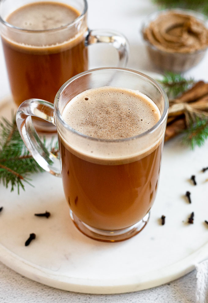 glass mug of spiced hot buttered rum next to cinnamon sticks and pine trees