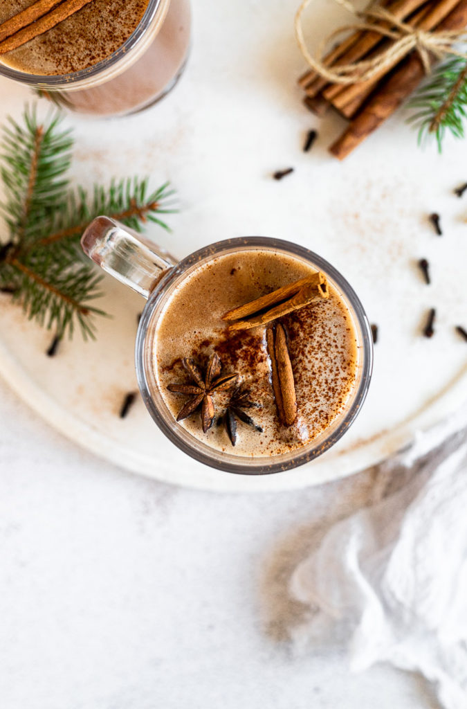overhead look into mug with hot buttered rum  with cinnamon sticks