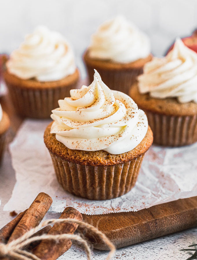 apple cider cupcake with cream cheese frosting on parchment paper and wood tray