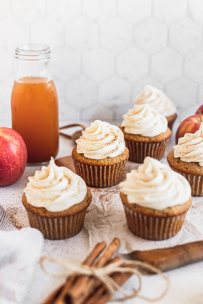 apple cider cupcakes on wood tray next to apple cider