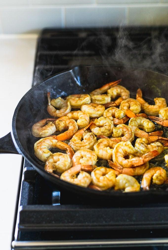 shrimp sautéing in cast iron skillet on stove