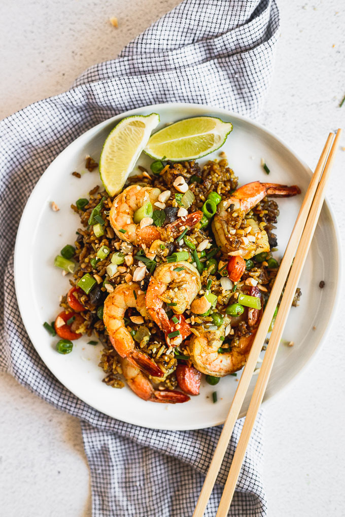 up close overhead view of white plate with curry shrimp fried rice wiht limes and chopsticks