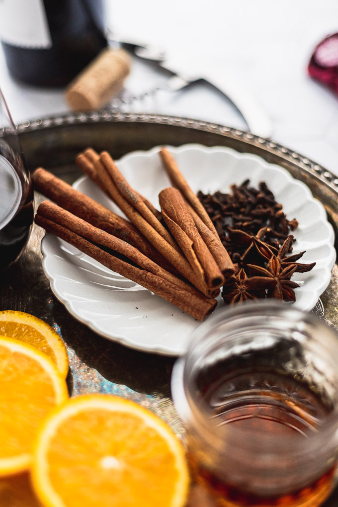 mulled spices on white plate next to oranges