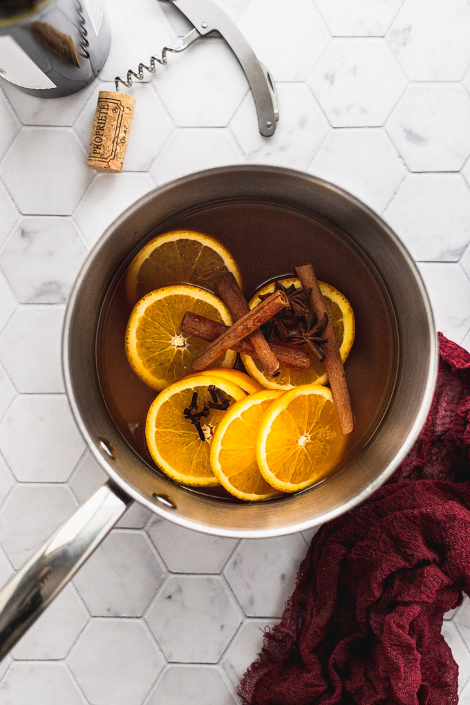 mulled spices with oranges and apple cider in sauce pan