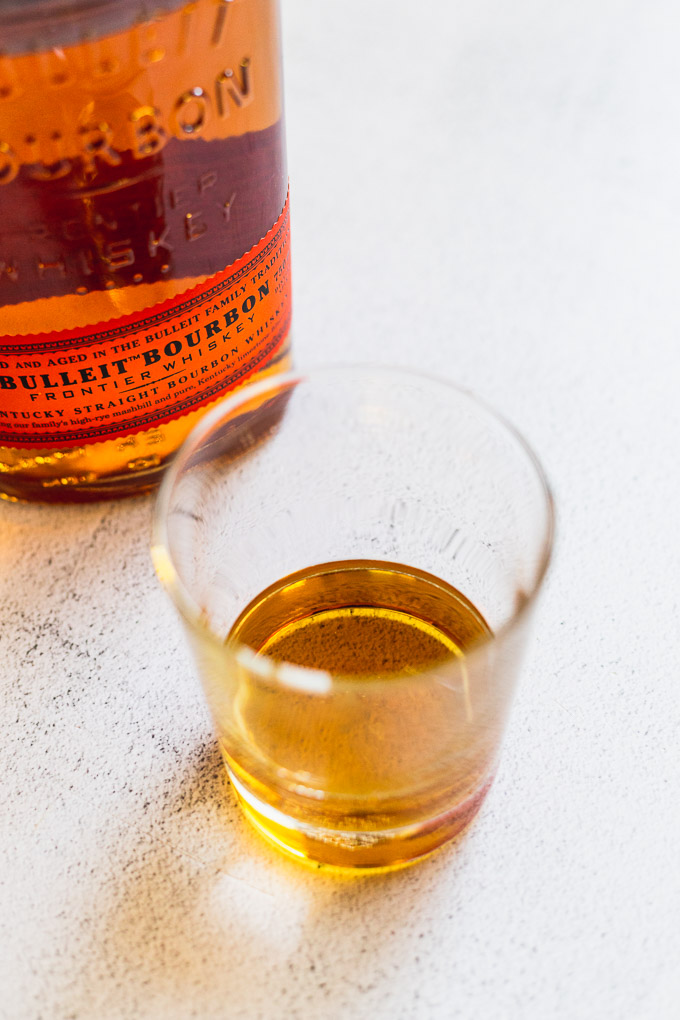 glass of bourbon next to bottle