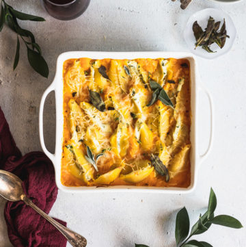 white baking dish with stuffed shells next to a spoon and greenery