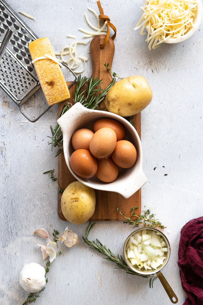 eggs, potatoes, rosemary, cheese, and garlic spread out