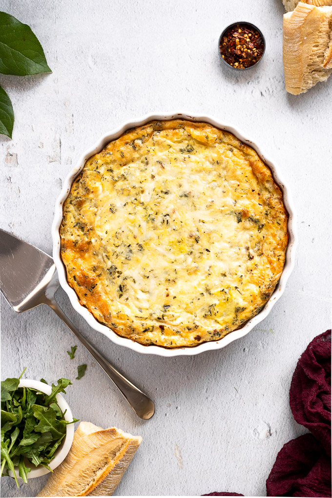 potato egg casserole in white tart pan with bread next to it and arugula