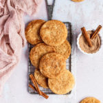 wire cooling rack with snickerdoodle cookies and cinnamon sticks next to pink linen
