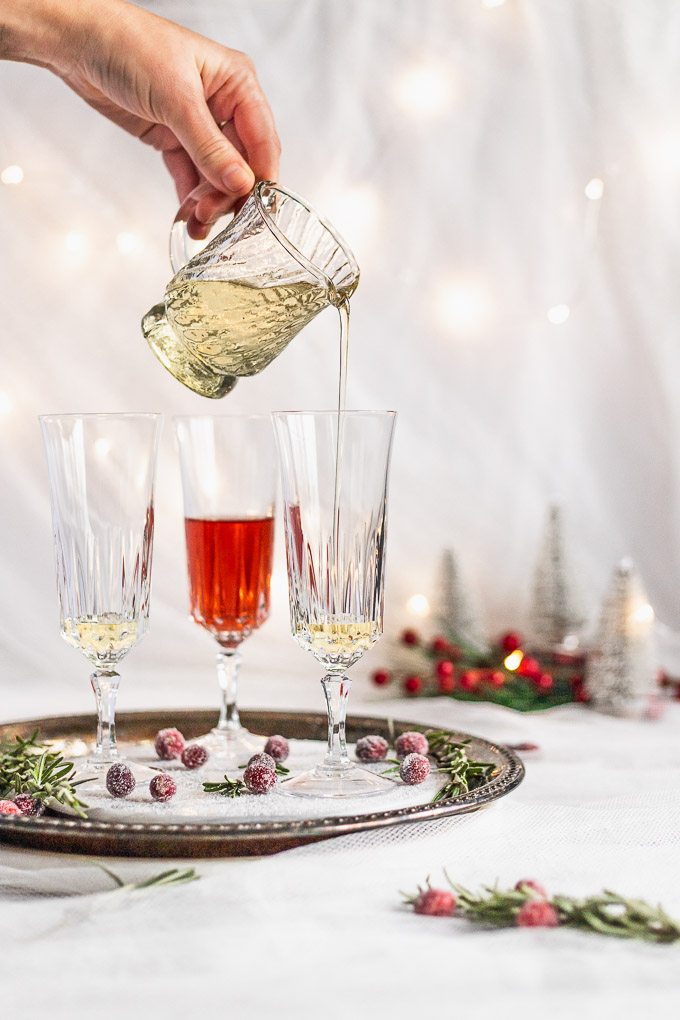pouring rosemary simple syrup into champagne flute