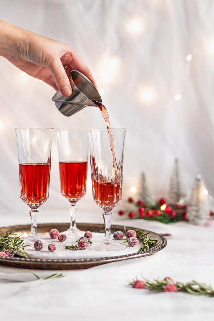 pouring cranberry juice into champagne flute with rosemary syrup
