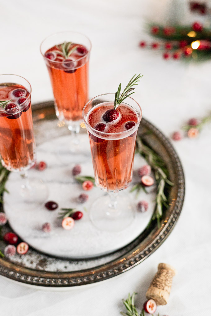 three glasses of cranberry rosemary prosecco on marble tray with sugar coated cranberries around
