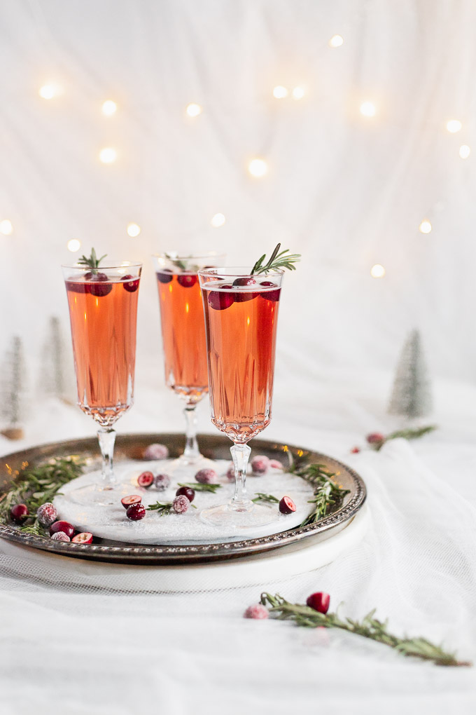 side view of cranberry prosecco on serving tray with rosemary sprig