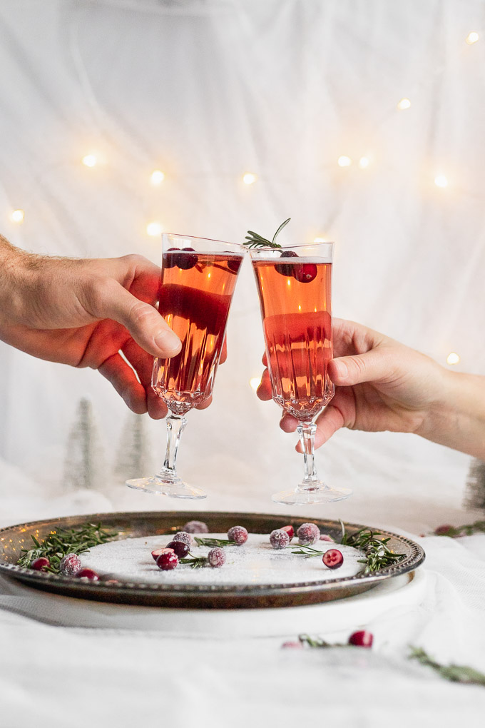 two people cheersing with cranberry rosemary prosecco