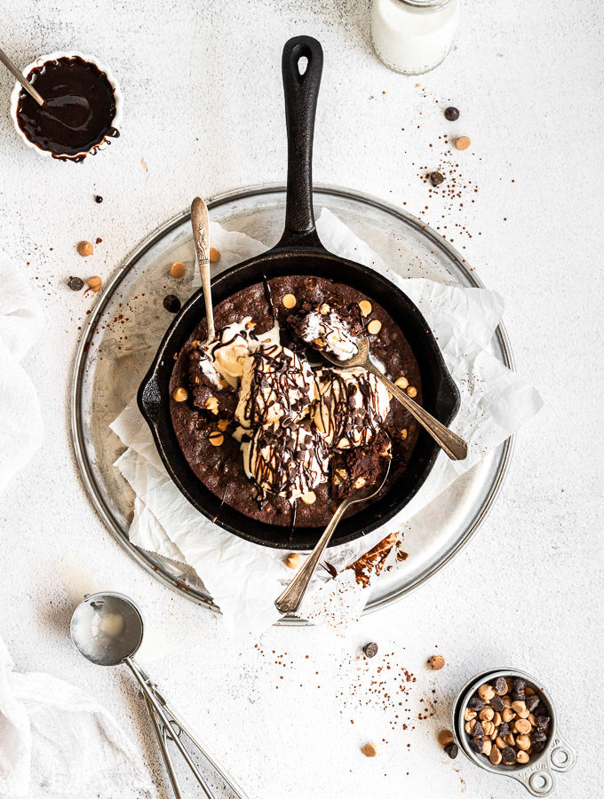 overhead brownie skillet with three spoons and ice cream with chocolate drizzle