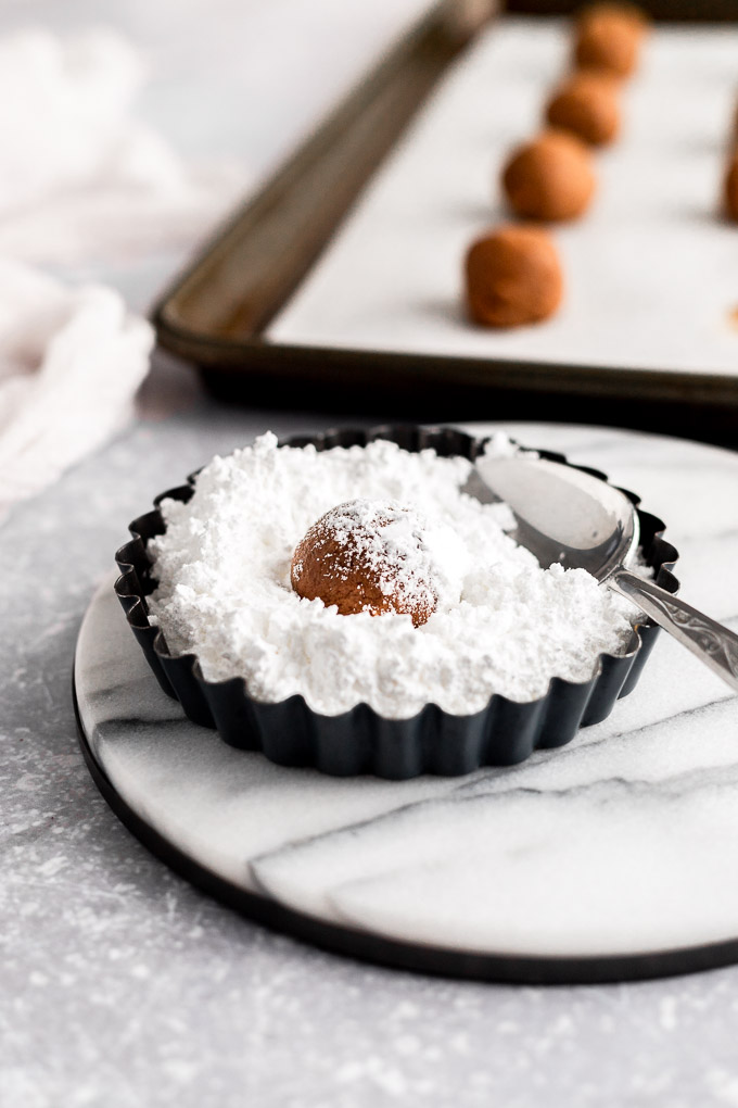 rolling cookie dough ball in powdered sugar