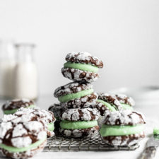 stack of chocolate mint sandwich cookies with milk in background
