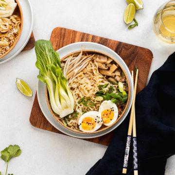 bowl of vegetarian ramen on wood tray with chopsticks