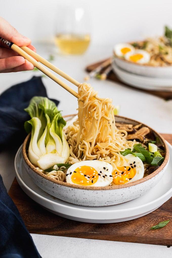 chopsticks picking up noodles in bowl of ramen