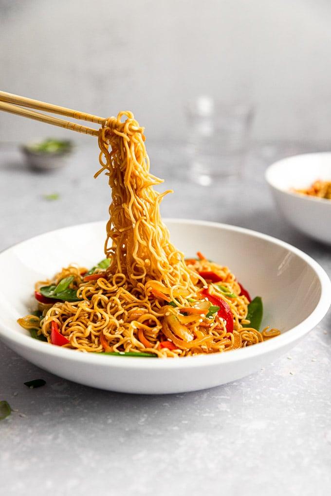 chopsticks pulling up vegetable lo mein noodles
