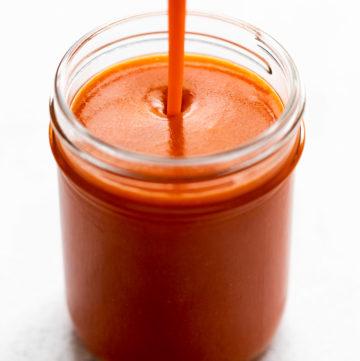 buffalo sauce pouring into glass jar
