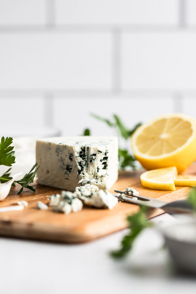 wedge of blue cheese with crumbles on cutting board