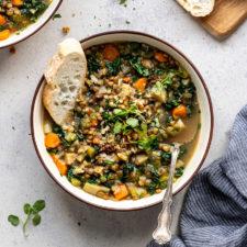bread in bowl of vegetable lentil soup