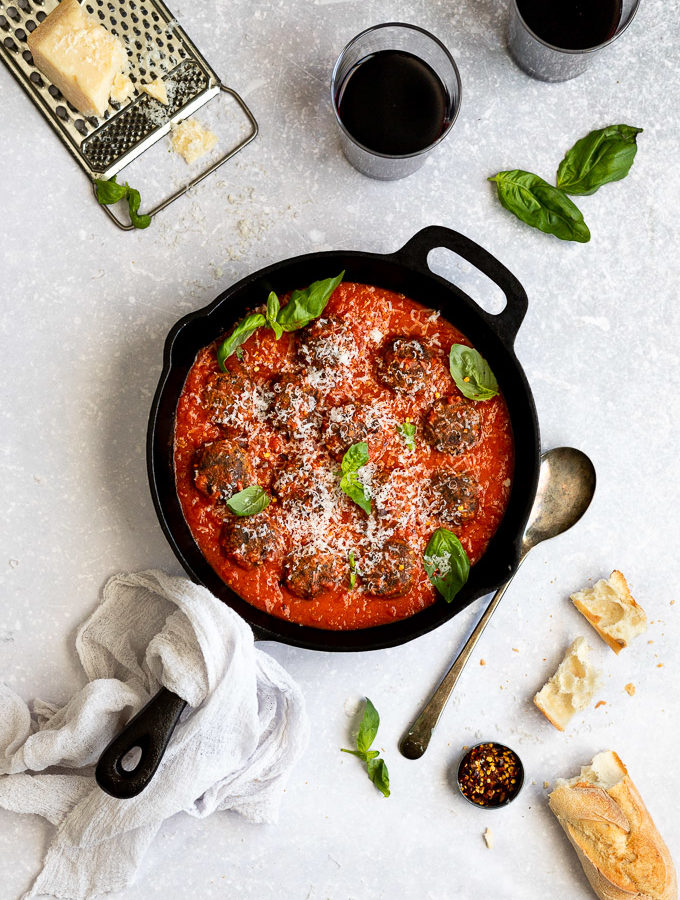 cast iron skillet with vegetarian meatballs and red sauce with parmesan cheese on top