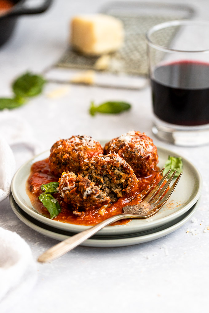 vegetarian meatballs on plate with fork, cut open next to wine glass