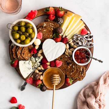 cheese board with heart of brie next to wine glasses