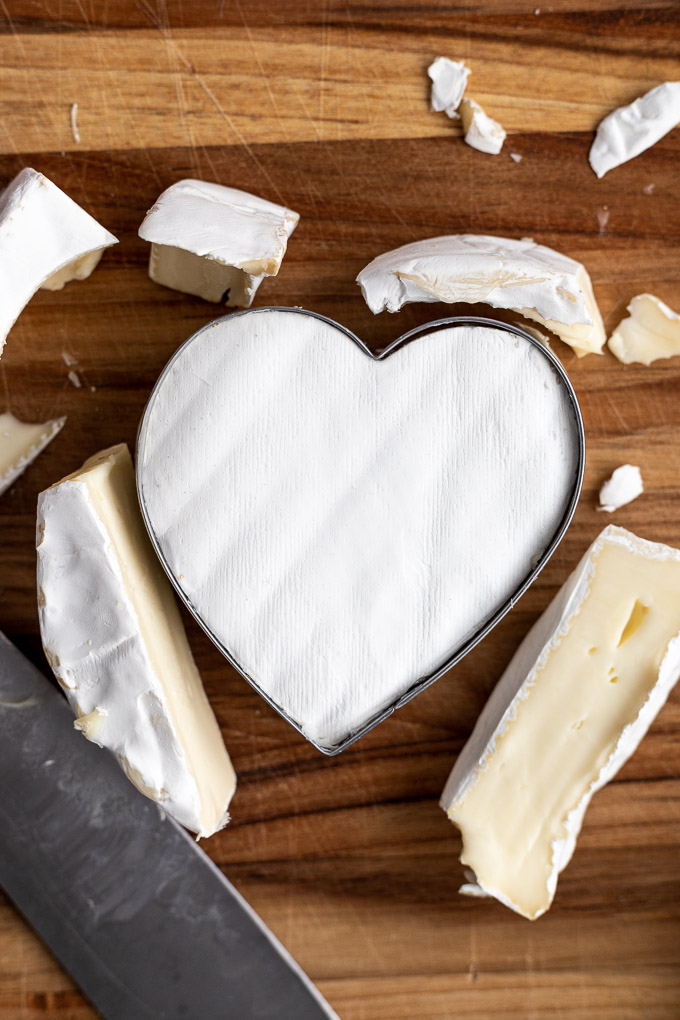 heart cookie cutter in brie wheel on cutting board