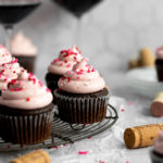red wine cupcakes on cooling rack with wine glasses and corks