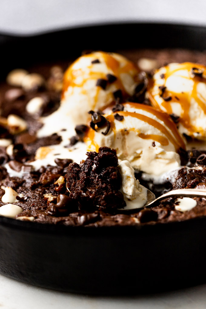 spoon with skillet cookie in the cast iron skillet