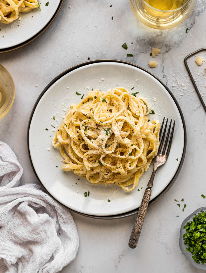 overhead plates of fettuccine alfredo with fork next to wine glass