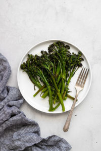 roasted broccolini on white plate with fork