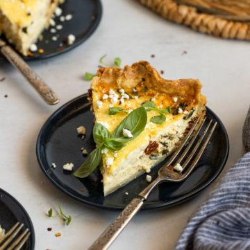 mediterranean quiche slice on plate with fork