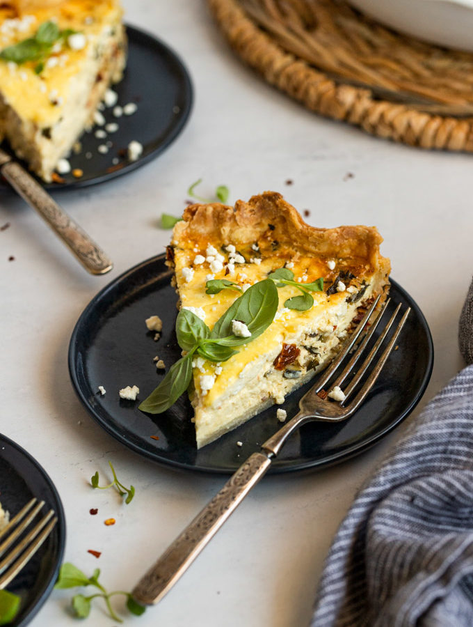 mediterranean quiche slice on plate with fork