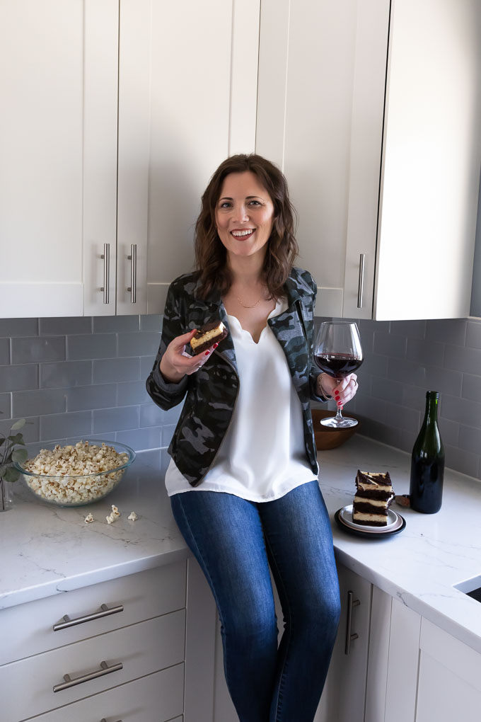 Becca is holding a brownie and a glass of wine.