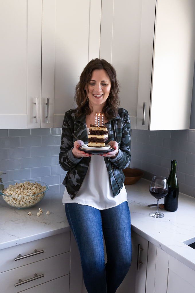 Becca holding plate of stacked brownies with lit candles.