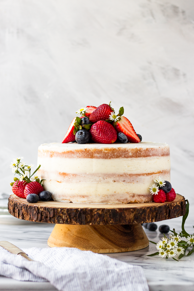 layered cake on wooden cake stand with berries and flowers
