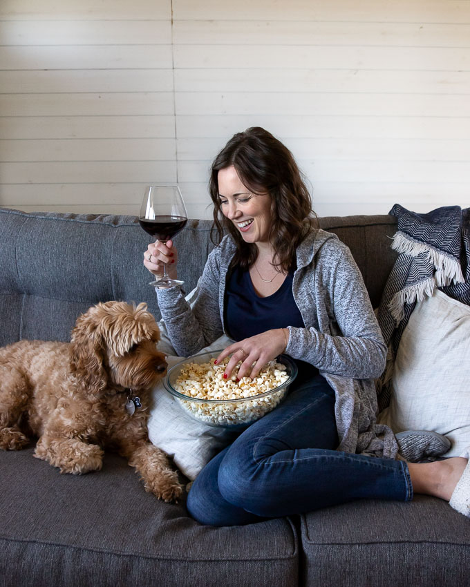 Becca on the couch holding a glass of wine and a bowl of popcorn with puppy next to her.