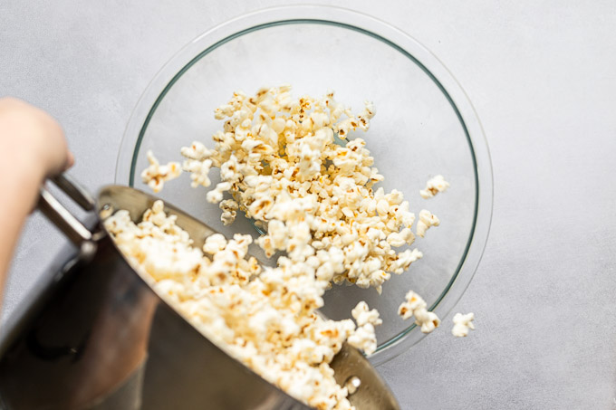 Pouring popcorn from stockpot to serving bowl.