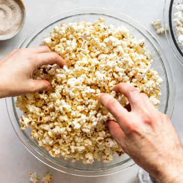 Two hands grabbing popcorn out of a bowl.