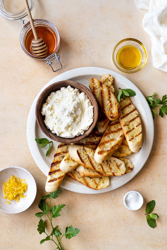 Large plate with bread, ricotta, next to lemon zest, honey, and olive oil.