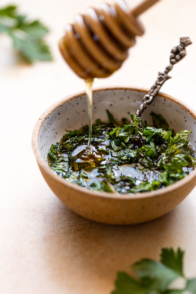 Honey drizzling into bowl of chopped herbs.