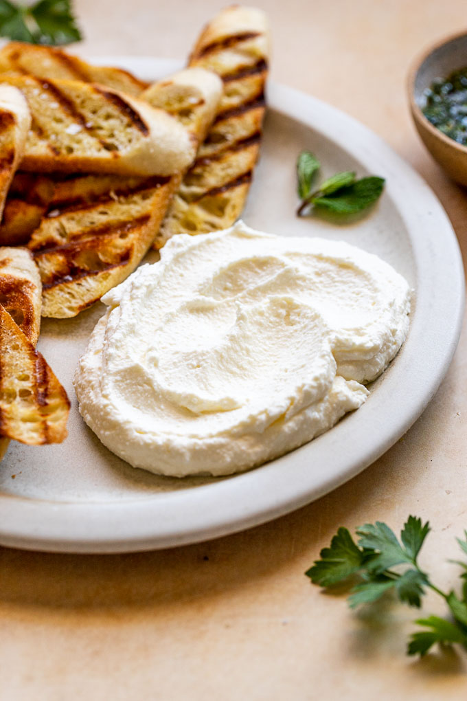 Plain whipped ricotta on a large white plate next to bread slices.