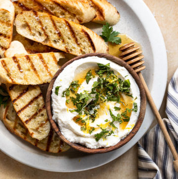A large white plate topped with grilled baguette slices and a wooden bowl filled with ricotta next to two wine glasses.